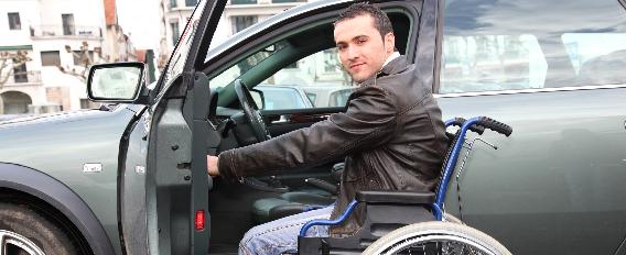 Homme en fauteuil roulant ouvre la portière de sa voiture