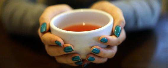 Tasse de thé tenue entre deux mains